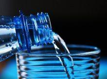 Wasser fließt in Glas über Wasserflasche