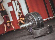 Aufnahme aus einem Crossfit Gym mit Hantel und Gürtel im Vordergrund und Trainer + Client im Hintergrund