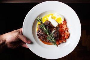 Keto Diät Mahlzeit auf einem weißen Teller mit Steak, Eiern und Thymian