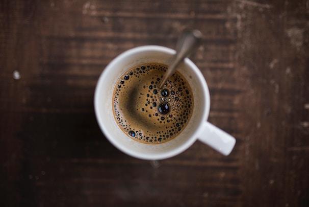 Bulletproof Coffee in weißer Tasse auf dunklem Holz